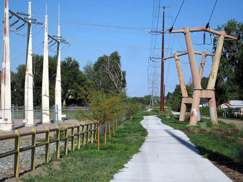Transmission towers next to bikeway and metal fences